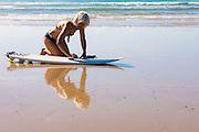 Woman surfer waxing surfboard on the beach, Sandy Beach, Coffs Harbor, NSW, Australia