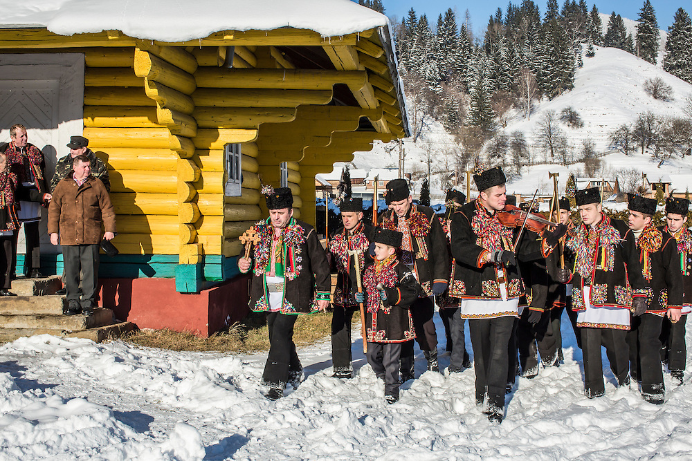ILTSI, UKRAINE - JANUARY 7: Men wearing traditional Hutsul clothing take part in Orthodox Christmas celebrations at Holy Trinity Church on January 7, 2015 in Iltsi, Ukraine. The men gather in groups and march around the church three times before spending twelve days traveling house to house singing songs until they've visited every home in the village. (Photo by Brendan Hoffman/Getty Images) *** Local Caption ***
