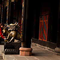 woman rubbing bronze statue for luck before entering temple at wenshu monastery
