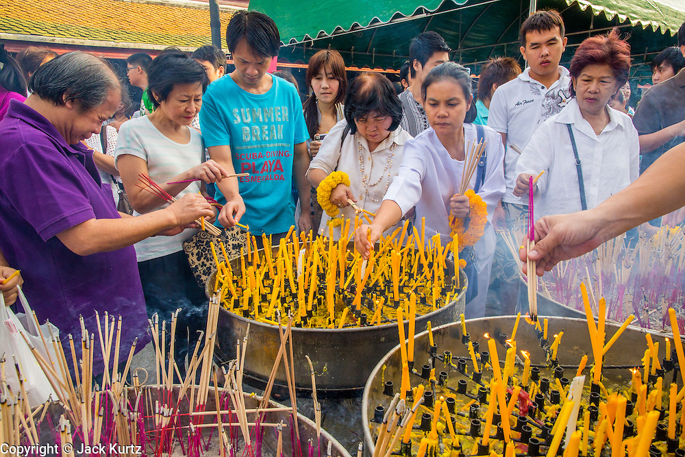 "01 JANUARY 2013 - BANGKOK, THAILAND:  People light candles and burn incense during a New Year's Day merit making service at Wat Suthat in Bangkok. Many Thais go to Buddhist temples and shrines to ""make merit"" for the New Year. The traditional Thai New Year is based on the lunar calender and is celebrated in April, but the Gregorian New Year is celebrated throughout the Kingdom.     PHOTO BY JACK KURTZ"