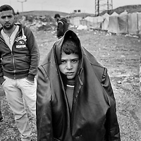 A Syrian refugee wears a coat over his head outside of his camp in Reyhanli, Turkey, Friday, March 16, 2012. The number of Syrian refugees in Turkey is now about 17,000. March 2012.