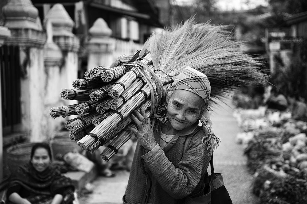 A woman selling hand made grass brooms in the morning market in Luang Prabang, Laos.