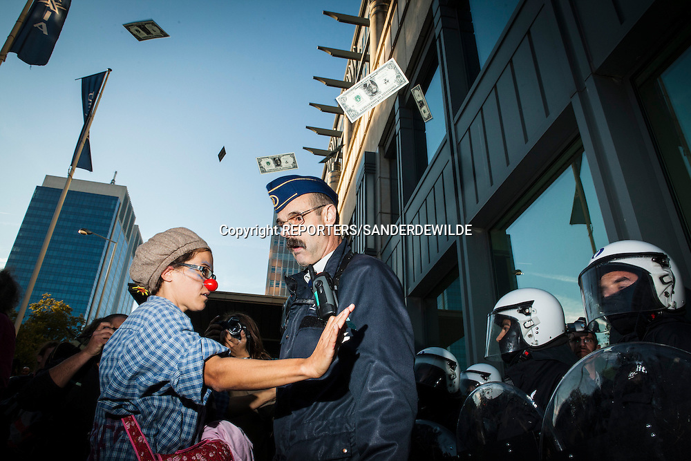 ndignados protests against the financial crisis and the power of banks and kapitalism. At the Dexia headquarters with fake dollars this girl confronts the police. Brussels Belgium 15 october 2011