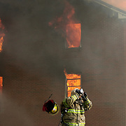 Photo by Gary Cosby Jr.    A firefighter is overcome by heat and strips off her air pack while battling a fire which consumed Victory Worship Center in Lawrence County, Alabama.