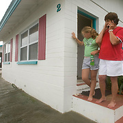 Vera Florence (C) talks on her cellphone as she stands outside with family friend Billie Jo Ross, 11, as their cottage at the Faraway Inn in Cedar Key, Florida is surrounded by the surge from Tropical Storm Alberto June13, 2006. REUTERS/Scott Audette