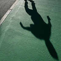 A teen skater does a trick in the parking lot of a shopping mall.  Photo by Matthew Healey