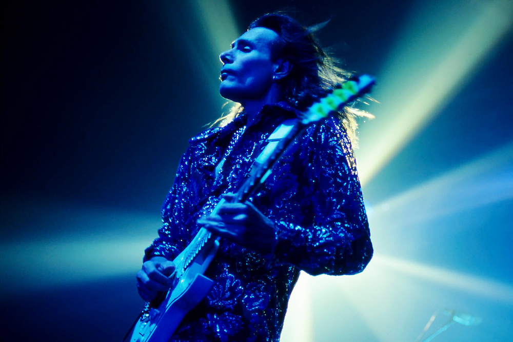 Steve Vai G-3 tour Houston, Texas. Blue light bathes Steve Vai as he plays his  Signature Jem Series electric guitar. White light beams shoot around him in every direction, glowing against a dark blue background.