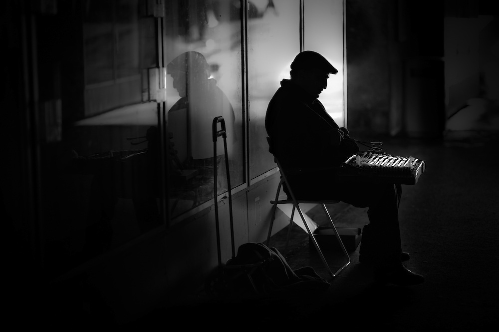 An elderly man plays a German Instrument