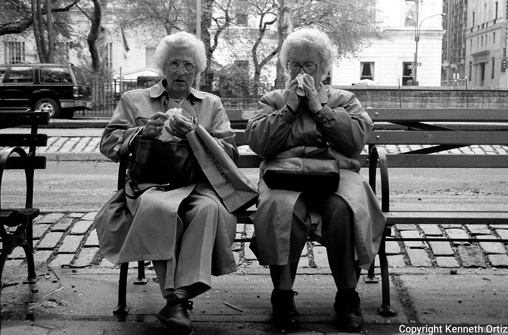 Two older woman sitting on a bench near the entrance of Central Park in New York City.