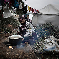 SYRIA, ATMEH. A woman cooking inside the camp for displaced Syrians in Atmeh on January 12, 2013, where there is no gas and small olive branches are the only wood available for fire. The camp is on the border with Turkey and is providing shelter to nearly 13,000 people; most of them are children. ALESSIO ROMENZI