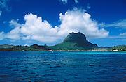 Mount Pahia and Vaitape village, seen from boat on lagoon; Bora Bora, Tahiti.