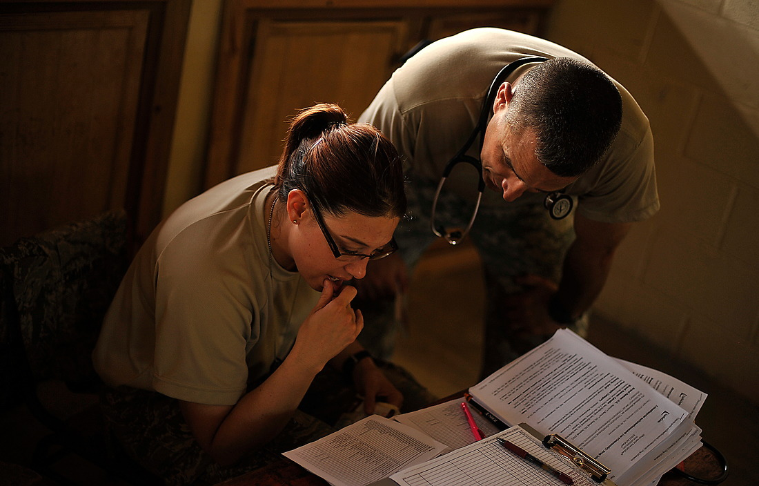 """Army Col. Matthew Rettke, the JTF-Bravo Medical Element commander and irst Lt. Daniela Feldhausen, a physician assistant look over some medical charts in the costal village of Batalla. """"This is a great opportunity for (medical personnel) to get out and practice medicine under some austere conditions,"""" said Col. Rettke. """"This is a very remote area, so it trains us on being able to pick up and move and ultimately prepare them for one of our main missions at JTF-Bravo, being able to respond to disasters."""" — © /"""