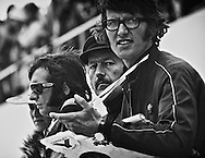 John Player Special Team Lotus principle and designer Colin Chapman and JPS Team Manager Peter Warr stand with 1972 World Champion Emerson Fittipaldi as they watch two-time World Champion Jackie Stewart shake down the new ELF Team Tyrrell-Ford 005 during the 1972 United States Grand Prix. <br /> <br /> Despite the strength of the Lotus team throughout the '72 season, their visible reaction to Stewart's speed in the Tyrrell suggested that they were now at a disadvantage to the more nimble car. <br /> <br /> The 25-year old Brazilian Fittipaldi won five of 11 races and handily took the championship from Jackie Stewart by 16 points driving the Chapman-designed John Player Special Team Lotus 72D. He became at the time the youngest F1 World Champion in history. <br /> <br /> However, the new Tyrrell-Ford was a completely new direction in design and with it, Stewart would go on to take pole position and win the race going away with a 40-second margin. <br /> <br /> Fittipaldi would retire from the race with suspension problems. <br /> <br /> During the 1973 season, Jackie Stewart would win his third World Driving Championship and ELF Team Tyrrell would win their second Constructor's Championship.