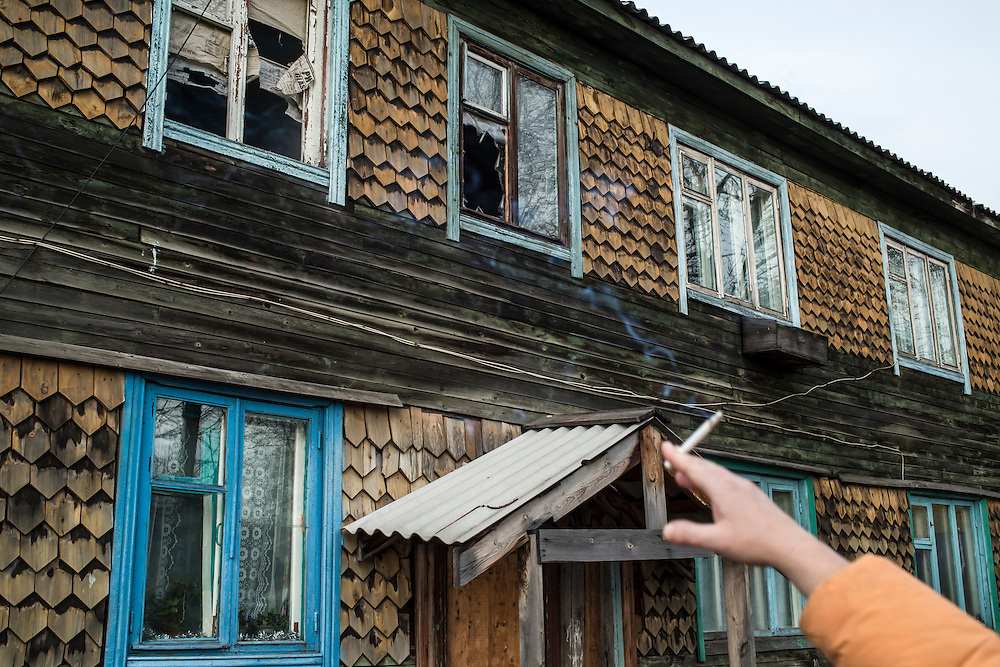 A woman points at broken windows in abandoned apartments on Wednesday, October 23, 2013 in Vydrino, Russia.