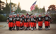 Roseville High School football players come on to the field before their game against Vanden, Friday Sept. 14, 2001. With the terrorists attacks on america the same week, they chose to carry an American flag during their march on the field..Neighbors/ Brian Baer.