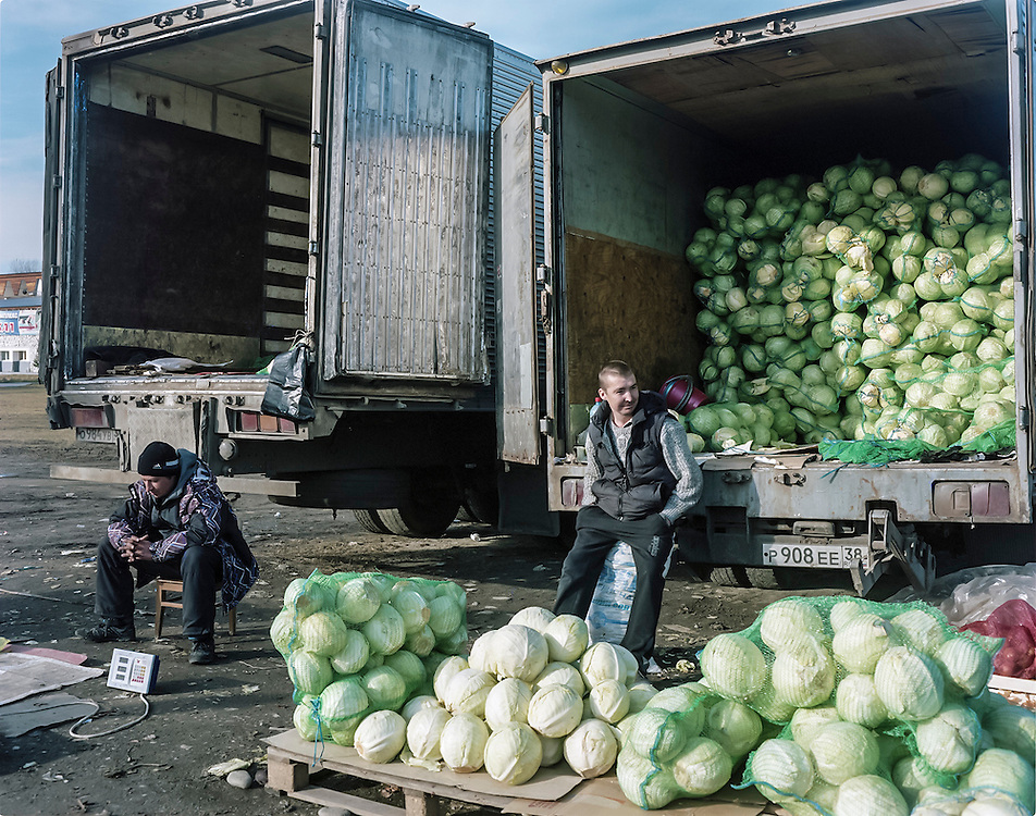 Men sell cabbage at a street market on Thursday, October 24, 2013 in Baikalsk, Russia.