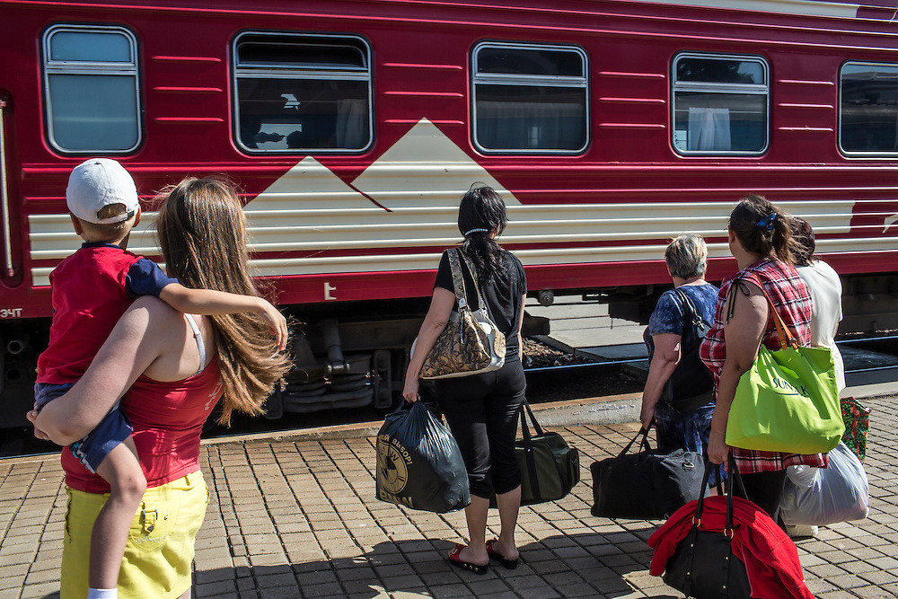People prepare to board a train traveling from Donetsk to Moscow, away from areas with heavy fighting, on Monday, July 28, 2014 in Yasinovataya, Ukraine.
