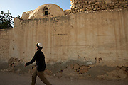 A young Jewish boy passes by an old home that once belonged to a Jewish family in the Hara Kebira neighborhood on the Tunisian Island of Djerba on May 26,2016. Five years after Tunisia's revolution, and a year after three deadly ISIS attacks, the 1,100 Jews in this tiny island community of Djerba say they do not feel threatened living in Tunisia.(Photo by Heidi Levine).