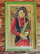 """A portrait of a Chinese woman hangs in a late 1800s restored frontier cabin in Nevada City, Montana, USA. In 1870, Chinese people (nearly all male) made up 10% of the territorial population of Montana. Territorial laws prohibited """"China Men"""" from owning placer claims, so they mined the leavings of others or performed laundry or domestic service, which was always in great demand. Today, Nevada City contains several fascinating Chinese buildings built about 1890, mostly moved here from Butte, Montana. Nevada City was a booming placer gold mining camp from 1863-1876, but quickly declined into a virtual ghost town. This fascinating town inspires you to imagination what life must have been like in early Montana when gold was discovered at nearby Alder Gulch. More than 90 buildings from across Montana have been gathered for preservation at Nevada City, mostly owned by the people of the State of Montana, and managed by the Montana Heritage Commission. In 2001, the excellent PBS television series """"Frontier House"""" used one of the buildings and its furnishings to train families in re-creating pioneer life. A miner's court trial and hanging of George Ives in the main street of Nevada City was the catalyst for forming the Vigilantes, a group of citizens famous for taking justice into their own hands in 1863-1864. Directions: go 27 miles southeast of Twin Bridges, Montana on Highway 287."""