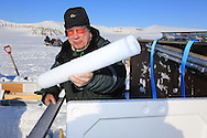 Glaciologist Tonu Martma of Tallinn University of Technology holds ice core taken from snow pit atop Kongsvegen glacier 750 meters (2460 feet) above sea level at Kongsfjorden; Svalbard, Norway.