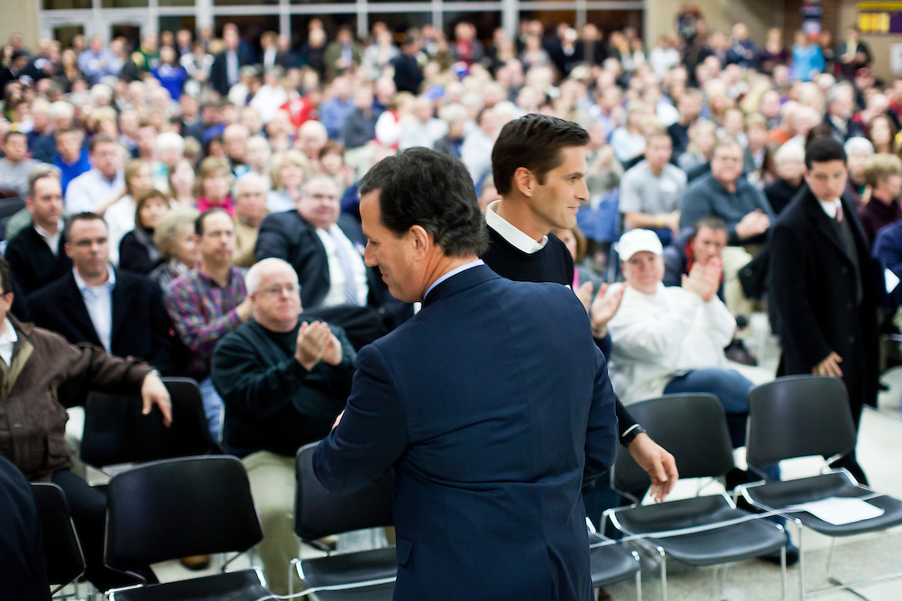 Republican presidential candidate Rick Santorum greets Josh Romney, son of fellow candidate Mitt Romney, at a caucus site at Summit Middle School on Tuesday, January 3, 2012 in Johnston, IA.