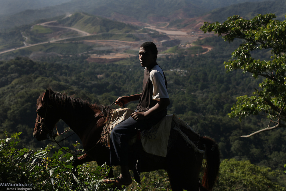 Natalio Gálvez Santo, 17, from La Cerca, rides a horse on the ridge of Cerro del Chivo. Looking south-southeast from the Cerro del Chivo peak, the massive El Llagal tailings pond is under development on the Southside of Highway 17. The extensive reservoir, nearly completed, will hold the toxic waste from Barrick and Goldcorp's Pueblo Viejo open-pit gold mine. Cotuí, Sánchez Ramírez, Dominican Republic. April 2012.