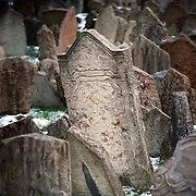 "SHOT 11/22/08 7:11:12 AM -  Tombstones in the Old Jewish Cemetery in Prague, Czech Republic. The Old Jewish Cemetery lies in the Josefov (the Jewish Quarter of Prague in the Czech Republic). It was in use from the early 15th century (the oldest preserved tombstone, the one of Avigdor Kara, dates back to 1439) until 1787. Its ancestor was a cemetery called ""The Jewish Garden"", which was found in archaeological excavations under the Vladislavova street, New Town..The numbers of grave stones and numbers of people buried there are uncertain, because there are layers of tombs. However, it has been estimated that there are approximately 12,000 graves. The most important personalities buried in the Old Jewish Cemetery are Yehuda ben Bezalel known as the Maharal Rabbi Löw (d. 1609), Mordechai Maisel (d. 1601), David Gans (d. 1613) a David Oppenheim (d. 1736). Prague is the capital and largest city of the Czech Republic. Its official name is Hlavní m?sto Praha, meaning Prague, the Capital City. Situated on the River Vltava in central Bohemia, Prague has been the political, cultural, and economic centre of the Czech state for over 1100 years. The city proper is home to more than 1.2 million people, while its metropolitan area is estimated to have a population of over 1.9 million. Since 1992, the extensive historic centre of Prague has been included in the UNESCO list of World Heritage Sites. According to Guinness World Records, Prague Castle is the largest ancient castle in the world. Nicknames for Prague have included ""the mother of cities"", ""city of a hundred spires"" and ""the golden city"". Since the fall of the Iron Curtain, Prague has become one of Europe's (and the world's) most popular tourist destinations. It is the sixth most-visited European city after London, Paris, Rome, Madrid and Berlin. Prague suffered considerably less damage during World War II than some other major cities in the region, allowing most of its historic architecture to stay true to form. It contai"