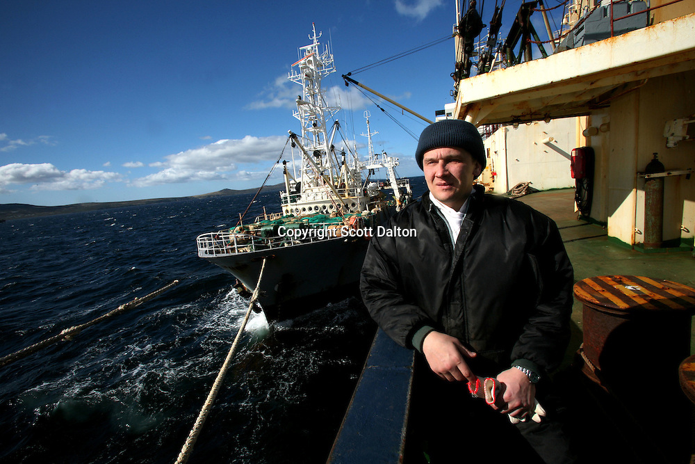 A Russian sailor looks out from the deck of a cargo ship while a fishing boat has it's catch of squid unloaded at sea off the coast of the Falkland Islands on Tuesday, March 20, 2007. The fishing industry has boomed in recent years, with boats from all over the world fishing the water off the islands. (Photo/Scott Dalton)