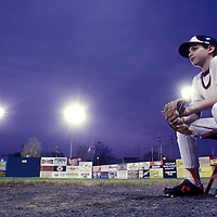 USA, Maryland, Hagerstown, Young ball boy watches minor league baseball game from sidelines