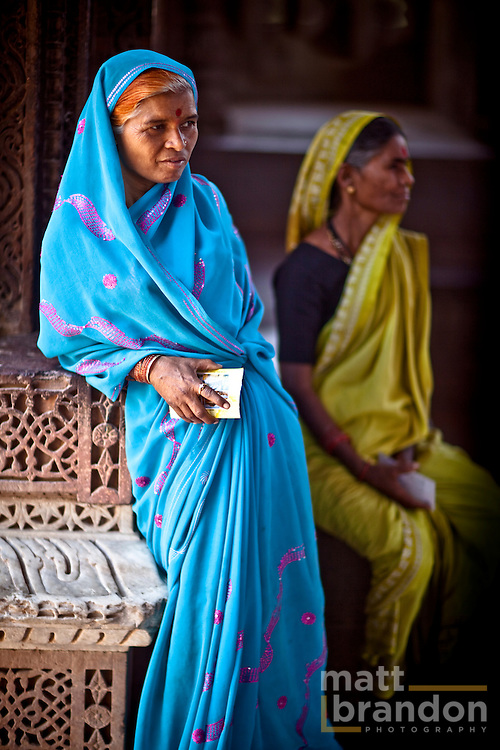 A woman in a blue sari rests as she waits for her family after visiting the Qtub Minar.