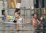 A man, dragging a woman on a floating door with supplies, waves off a rescue boat in flooded New Orleans August 30, 2005.  Hurricane Katrina devastated the town and surroundings and looting was reported in the area. Floodwaters engulfed much of New Orleans on Tuesday as officials feared a steep death toll and planned to evacuate thousands remaining in shelters after the historic city's defenses were breached by Hurricane Katrina.