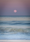 The full Hunter's Moon rising over breaking waves at Nauset Beach in Orleans.