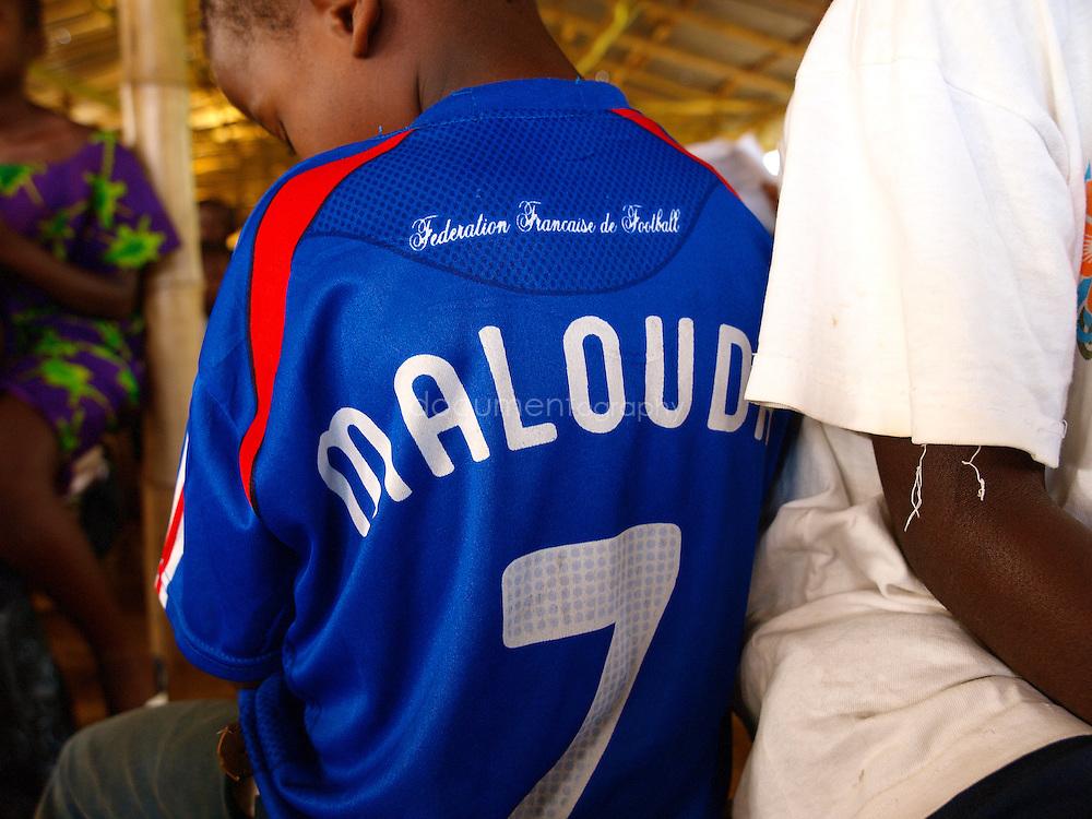 A pupil wearing a Malouda shirt at J.S. Varfley School, Kingsville #7, Liberia.
