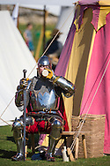 McG0064278<br /> A performer in heavy armour cools down with a drink at Portchester Castle in Hampshire where events have been taking place to mark the 600th anniversary of the battle of Agincourt. <br /> In 1415 soldiers left from the castle, now managed by English Heritage, for northern France where they went on to face the French in a muddy farmer's field.<br /> Picture date: Saturday August 8, 2015.<br /> Photograph by Christopher Ison &copy;<br /> 07544044177<br /> chris@christopherison.com<br /> www.christopherison.com