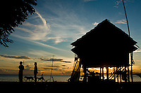 House, people and dogs silhouette against sunrise in Central Sulawesi, Indonesia