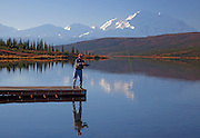 Alaska. Fly Fishing from the canoe dock on Wonder Lake, with Mt. McKinley in the background, Denali National Park (MR).