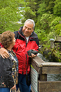 "USA, Alaska,Tourists enjoy the beautiful scenery of Ketchikan Creek which runs under Ketchikan's historic ""Creek Street"".MR"
