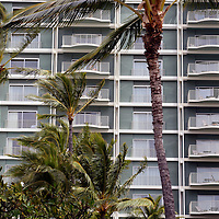 Palm trees compliment the facade of The Kahala Hotel & Resort in Honolulu, Hawaii.