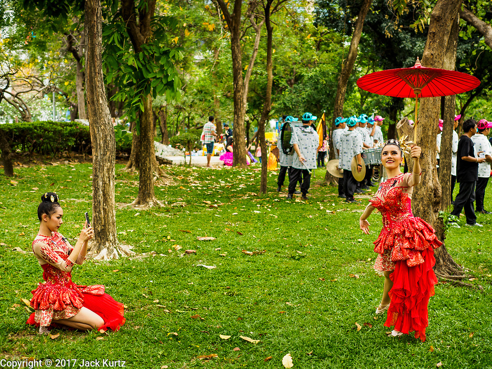 """08 APRIL 2017 - BANGKOK, THAILAND: Entertainers take photos of each other before the """"Amazing Songkran"""" festival in Benchasiri Park in Bangkok. The festival was sponsored by the Tourism Authority of Thailand to highlight the cultural aspects of Songkran. Songkran is celebrated in Thailand as the traditional New Year's Day from 13 to 16 April. Songkran is in the hottest time of the year in Thailand, at the end of the dry season and provides an excuse for people to cool off in friendly water fights that take place throughout the country. Songkran has been a national holiday since 1940, when Thailand moved the first day of the year to January 1. Songkran 2017 is expected to be more subdued than Songkran usually is because Thais are still mourning the October 2016 death of revered King Bhumibol Adulyadej.       PHOTO BY JACK KURTZ"""