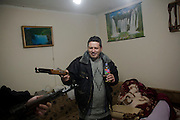 Uros Popovic at his home on the hill above Velika Hoca. He is drinking homemade rakija and showing off his wartime AK-47...Orthodox Christmas (January 7) in the Serbian village of Velika Hoca, Kosovo.