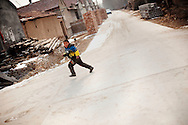 A boy runs through the town of Huji in the province of Shandong, China, Friday, Jan. 28, 2011. Despite record cotton prices last year, some farmers are storing their harvest of cotton and are holding out for even higher prices, hoping to help overcome higher costs of fertilizer and labor, which have both risen 20% in the past year..CREDIT:Keith Bedford for The Wall Street Journal.Slug: COTTON