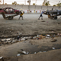 Four men push stripped car bodies to be sold as scrap metal for cash in the neighborhood of Cite Soleil in Port Au Prince, Haiti, March 31, 2011.