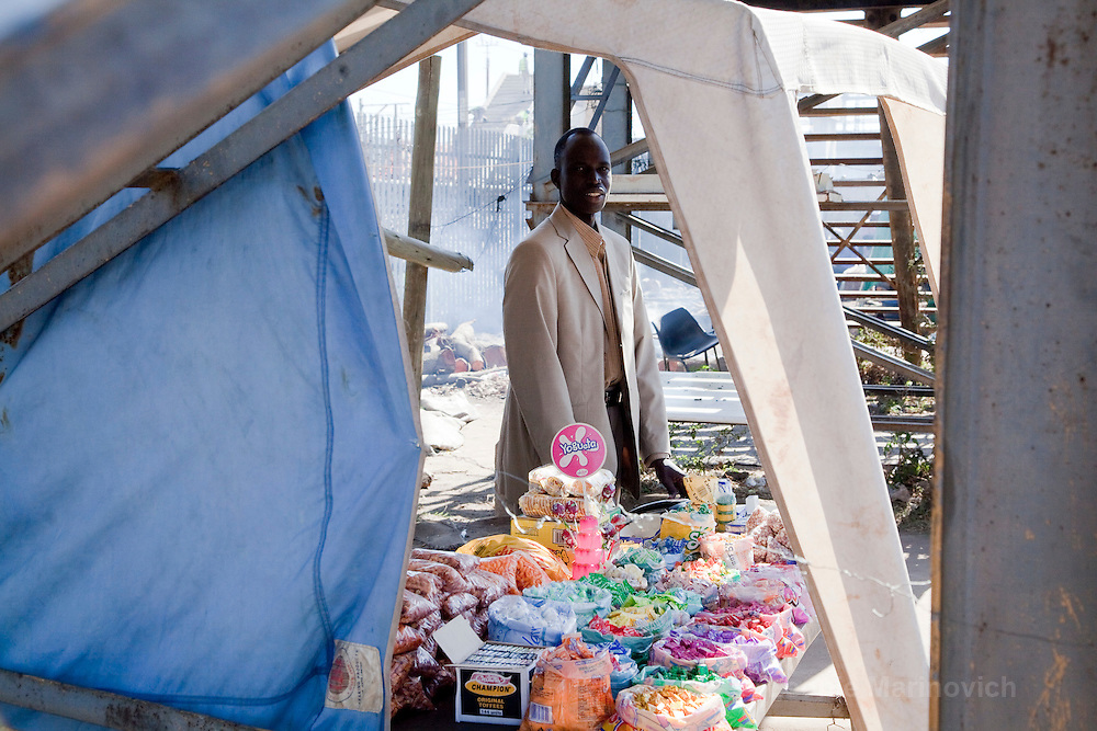 """1 July 2009, Sudanese """"Lost Boy"""" Aher Arop Bol at his spaza shop in Wonderboom, Pretoria and at the home of Sannie Meiring where he boards. He was born in a Dinka village in the Bahr el Ghazal region of Southern Sudan.  Bol now lives in Pretoria. He runs a spaza shop which enables him to pay his UNISA fees (he is studying law) and maintain his two brothers, with whom he has been reunited, at a boarding school in Uganda. Bol actively identifies himself as a """"lost boy"""", one of the tens of thousands of Sudanese children who were forced to leave their homeland because of their country's civil war."""