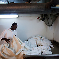 """Ali a sudanese refugee separates towels from sheets as he works in the laundry of the Royal Beach Hotel on February 28 2011. The municipality hung 1,500 red flags around the city as a sign of warning and put up hundreds of banners reading: """"Protecting our home, the residents of Eilat are drawing the line on infiltration."""" Eilat Mayor Meir Yitzhak Halevi said that 10 percent of the city's population was currently made up of migrants and that the residents feel that the city has been conquered...Photo by Olivier Fitoussi."""