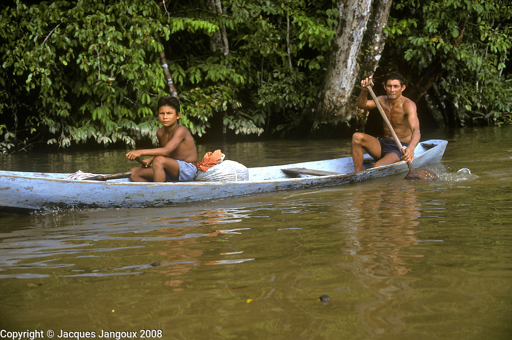 Caboclo, or mixed blood rural people, father and son in dugout canoe in Amazon estuary, Para, Brazil.