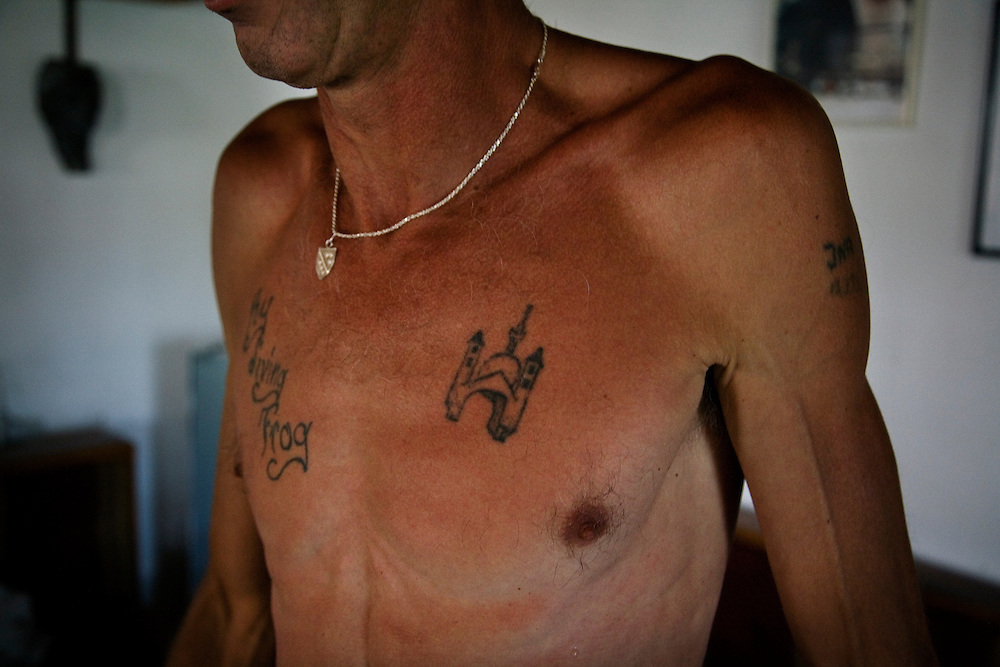 """Adem Mocca Pajevic, 50, recently returned to Mostar after 14 years living in Kentucky, USA. He is a war veteran and a professional diving coach who first leapt from the Old Bridge in 1975. He now spends his days as a Mostari in his hometown. The tattoos on his chest read """"Kentucky Diving Frog"""" and an image of the Old Bridge and a Mosque...Divers and tourists at Mostar's famous Old Bridge (Stari Most) in Bosnia and Herzegovina. This bridge is the city and region's biggest tourist attraction and there are busses full of tourists coming in from Sarajevo and Dubrovnik, Croatia. For 25euros tourists can train to jump from the bridge themselves, under supervision from the """"professional"""" Mostar divers known as the Mostari. .."""
