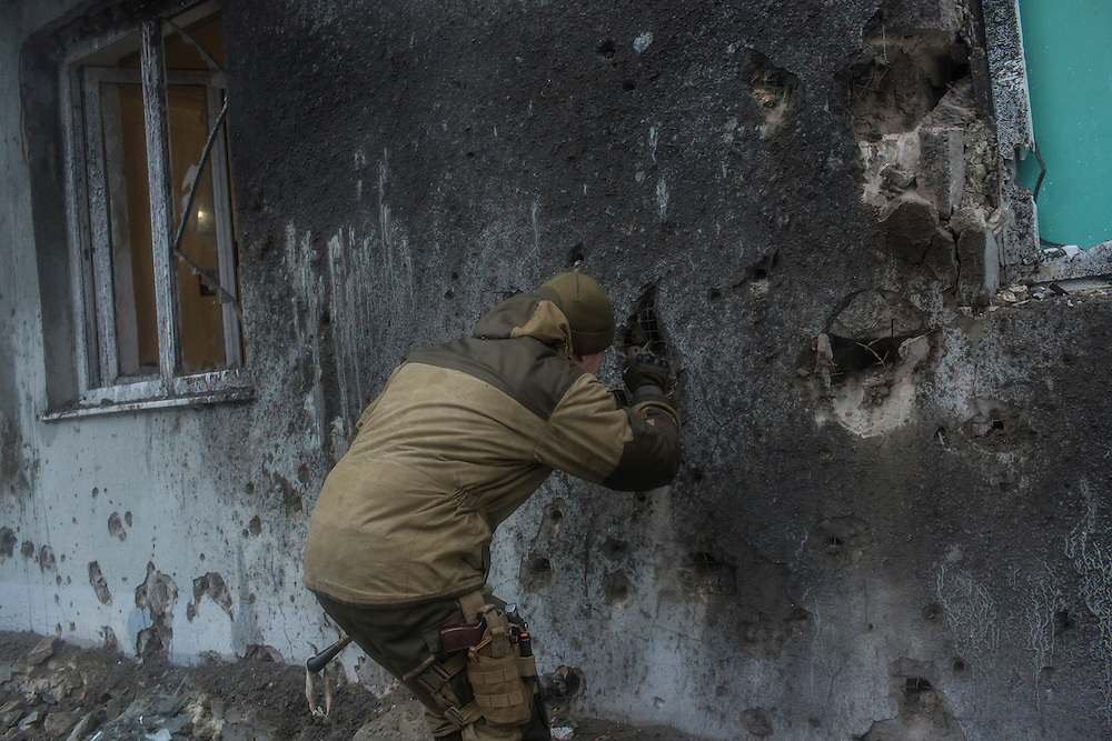 DONETSK, UKRAINE - JANUARY 30, 2015: A pro-Russia rebel extracts a piece of shrapnel from the wall of an apartment building after a shell landed just outside in Donetsk, Ukraine. At least two people were killed on the sidewalk when another shell landed just around the corner, and at least five died when a shell landed in the parking lot of a nearby humanitarian aid distribution center. CREDIT: Brendan Hoffman for The New York Times