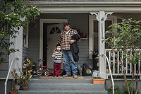 Landscape worker Alejandro Swarez is welcomed home by one of his housemates, three year old Alex, on the porch of their home on Cedar Street in Calistoga.
