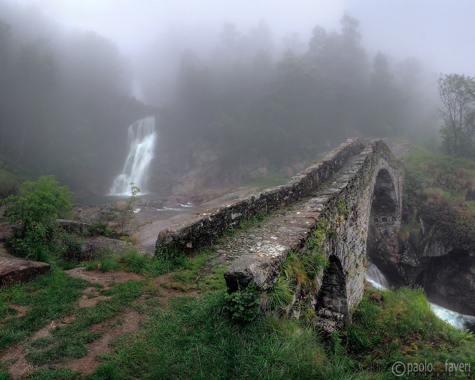 Taken on a late springtime evening, under a thick fog and some light rain. This is the stone bridge that spans the Ribordone stream in Val Chiusella, Piedmont, Italy..The bridge probably dates back to the XV-XVI century, and it's a fine example of engineering of that time. This is a stitch of four vertical takes.