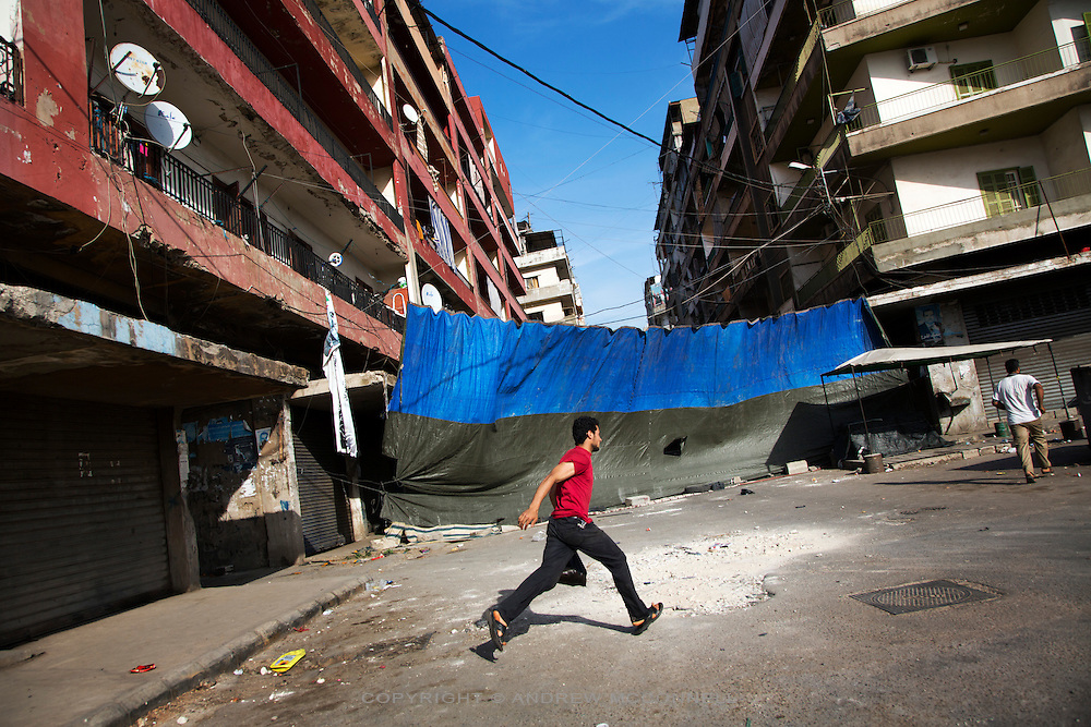 Two men run past a tarpaulin sheet draped across a street in order to protect residents from sniper fire coming from the Jabel Moshen neighbourhood, in Bab al-Tabbaneh, Tripoli, Lebanon. Bab al-Tabbaneh is a Sunni muslim quarter which sits directly below the Alawite muslim quarter of Jabel Moshen. The two sides have been involved in regular clashes over the past 2 years, with the fighting directly linked to the civil war in Syria.